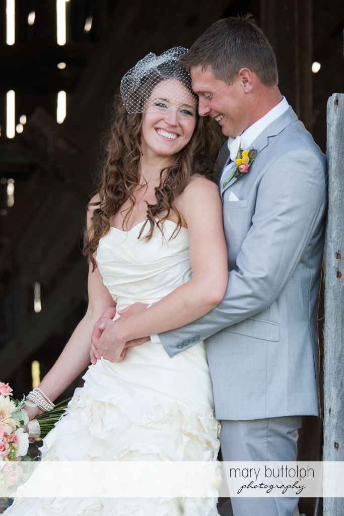 Couple share a tender moment near an old barn at the Inns of Aurora Wedding