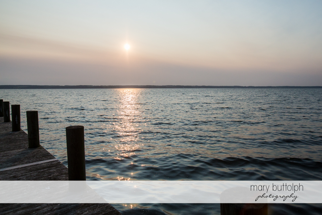 The sun sets on the peaceful waters of the lake at the Inns of Aurora Wedding