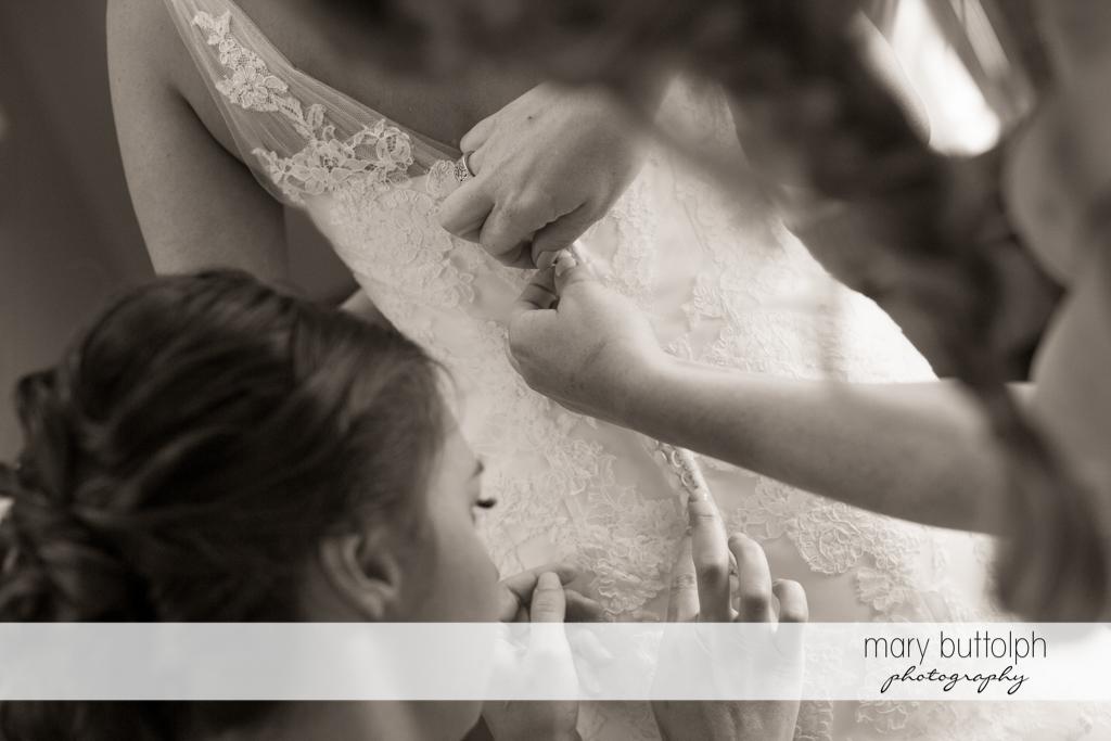 Friends fix the bride's wedding dress at Arrowhead Lodge Wedding