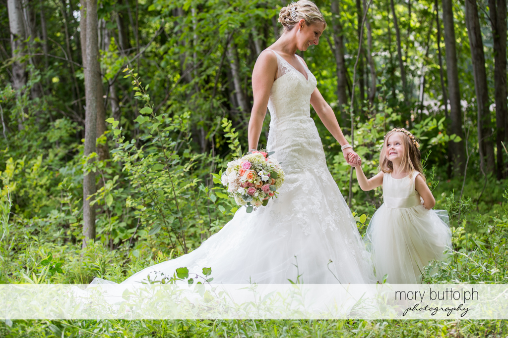 Bride and young girl stroll in the garden at Arrowhead Lodge Wedding