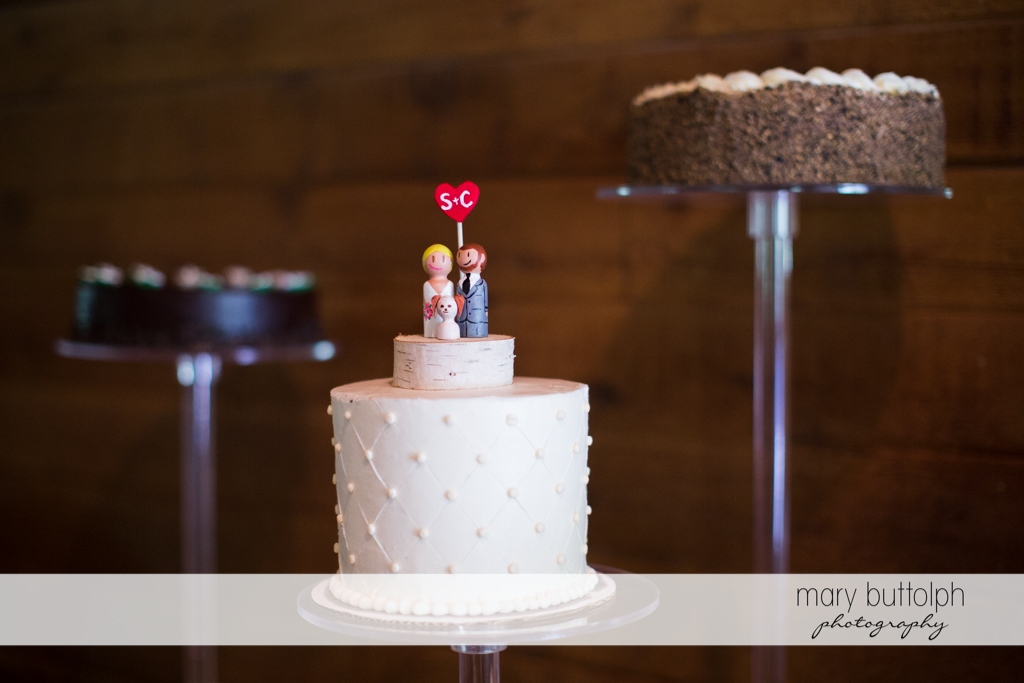 Couple's wedding cake with a unique cake topper at Arrowhead Lodge Wedding