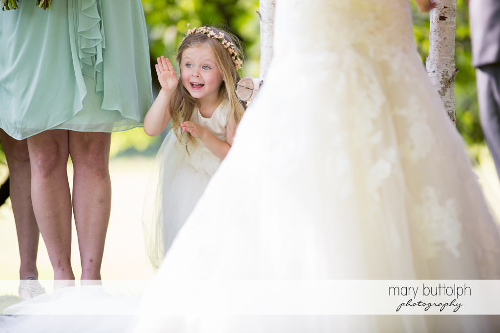 Flower girl waves to guests at Arrowhead Lodge Wedding