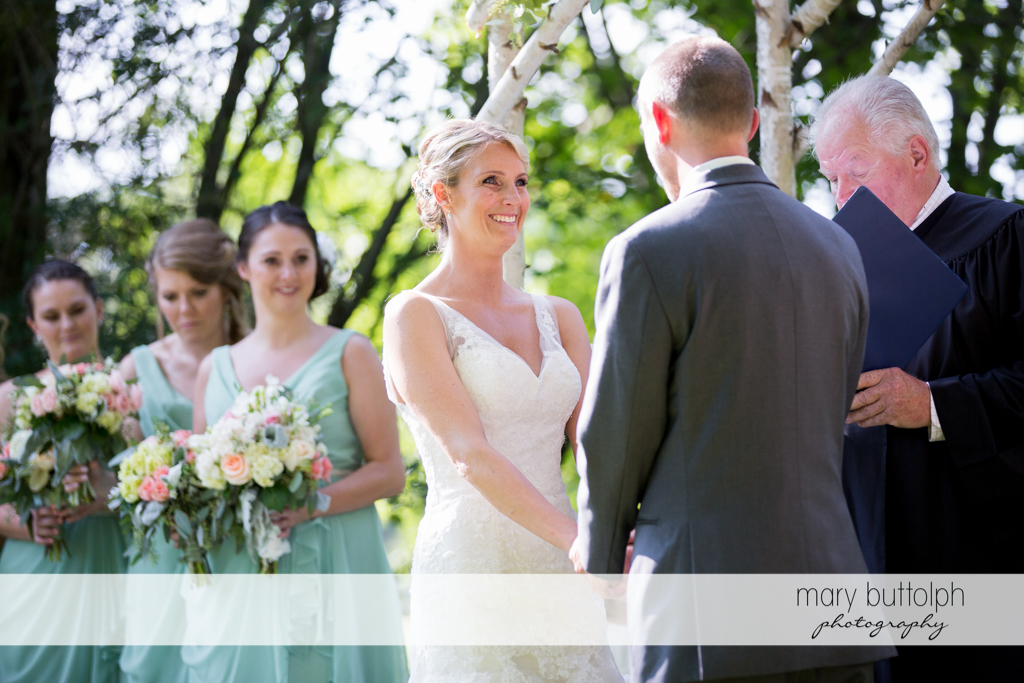 Bride faces the groom in the garden at Arrowhead Lodge Wedding