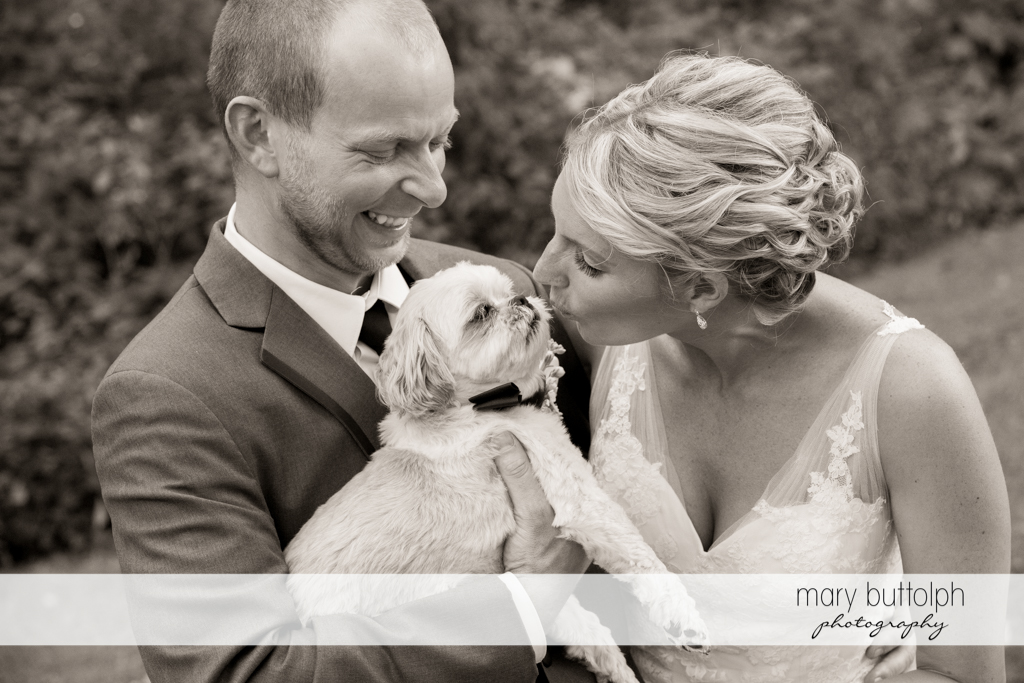 Bride kisses her pet dog as the groom watches at Arrowhead Lodge Wedding