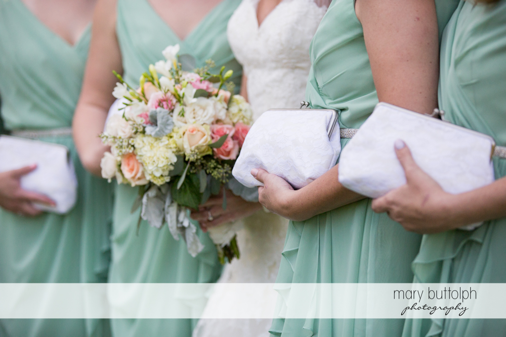 Close up shot of the bride's bouquet and the bridesmaids' white handbags at Arrowhead Lodge Wedding