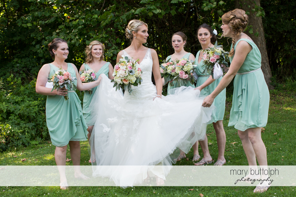 Bridesmaids hold the bride's wedding dress in the garden at Arrowhead Lodge Wedding