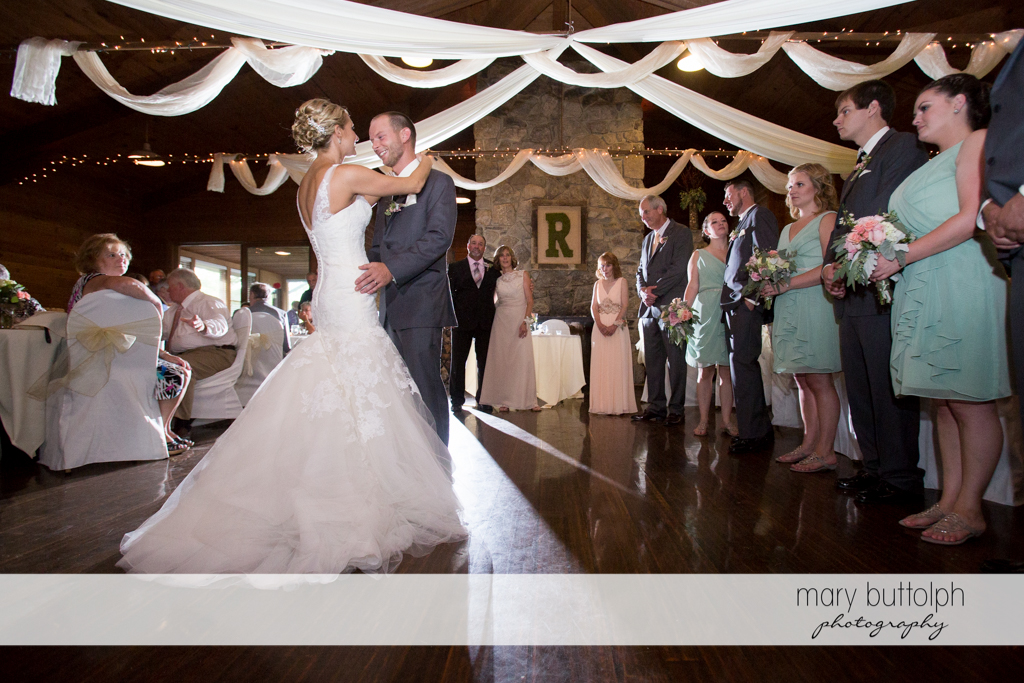 Couple dance as guests look at Arrowhead Lodge Wedding