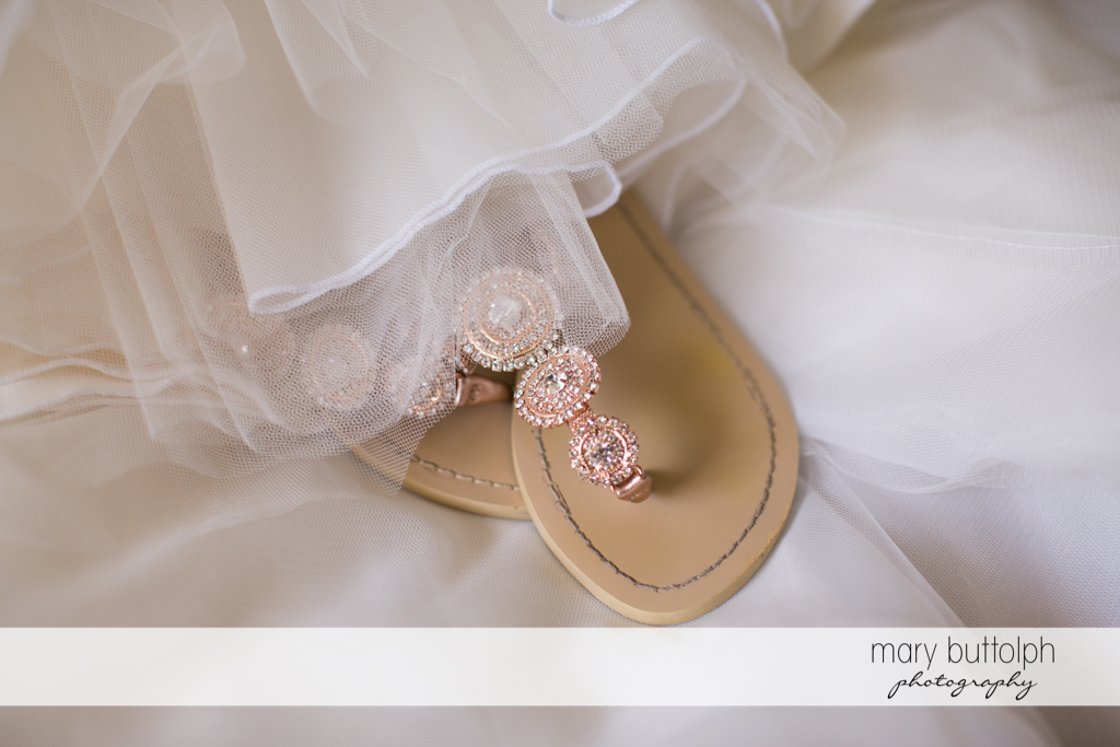 Bride's wedding sandals are partly covered by her wedding gown at Arrowhead Lodge Wedding