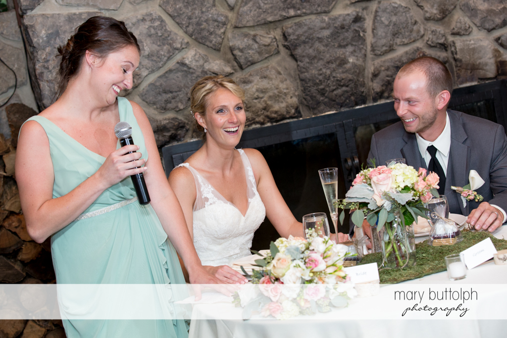 Couple and bridesmaid share a light moment at Arrowhead Lodge Wedding
