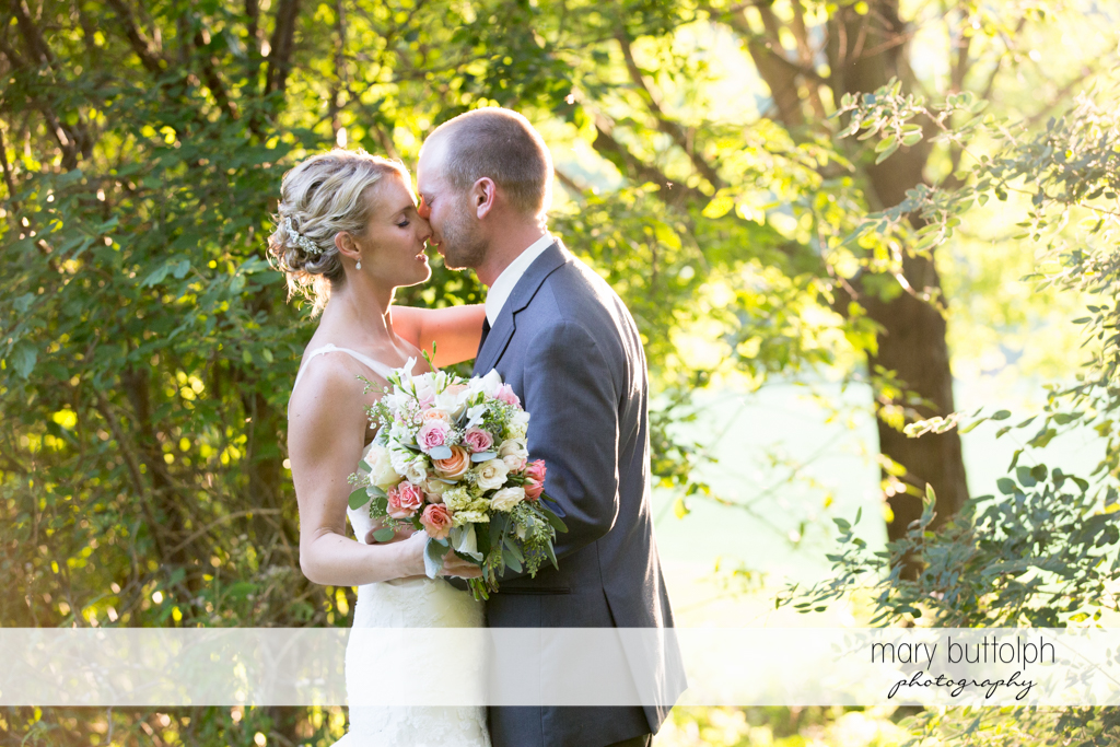 Couple share a tender moment in the garden at Arrowhead Lodge Wedding