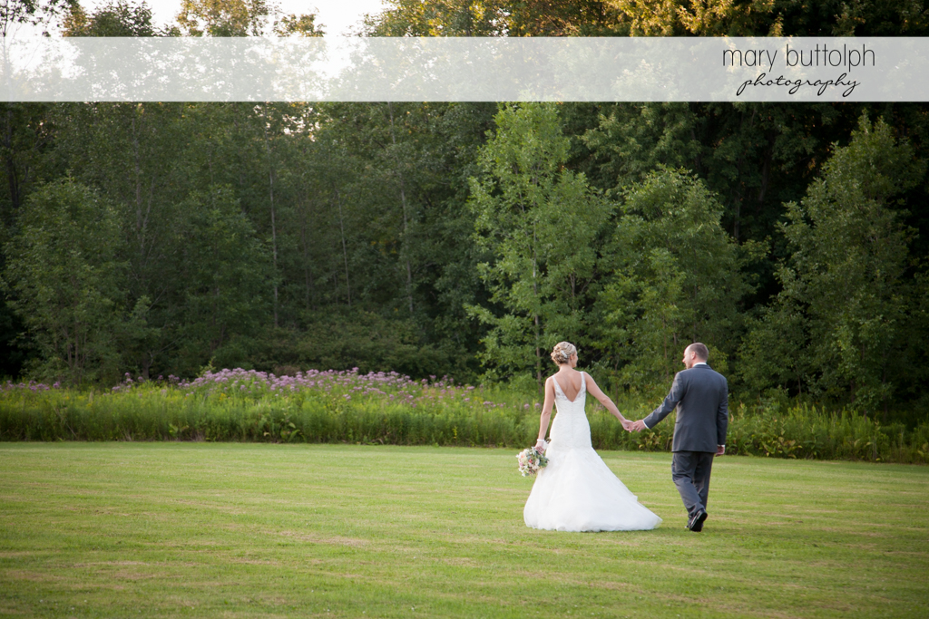 Couple stroll in the garden at Arrowhead Lodge Wedding