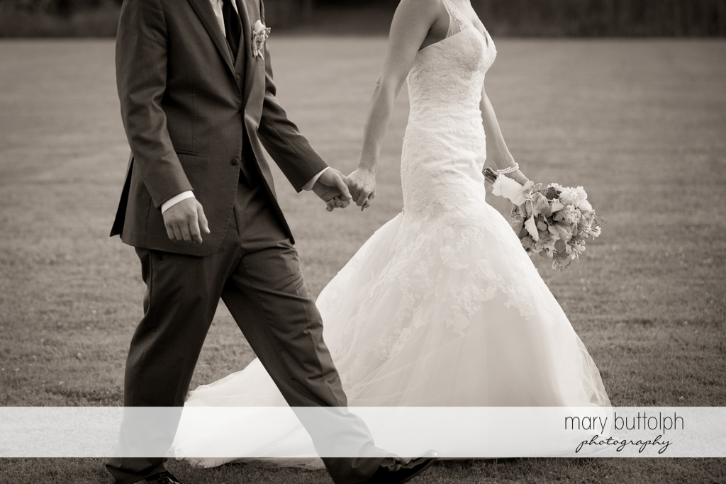 Couple hold hands as they walk in the garden at Arrowhead Lodge Wedding