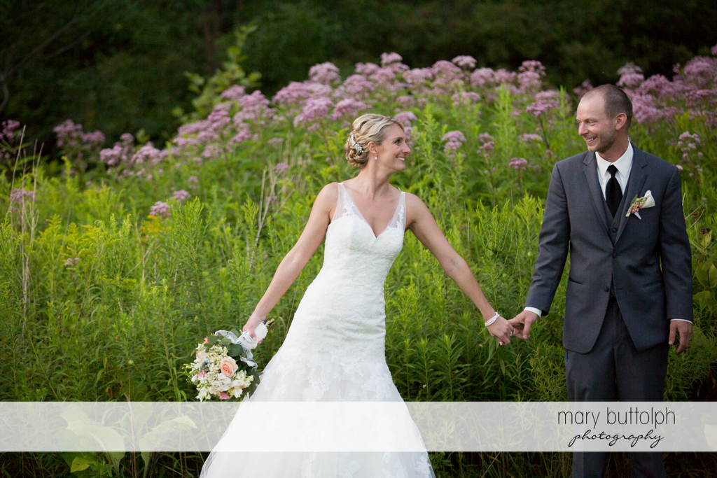 Couple hold hands while walking in the garden at Arrowhead Lodge Wedding