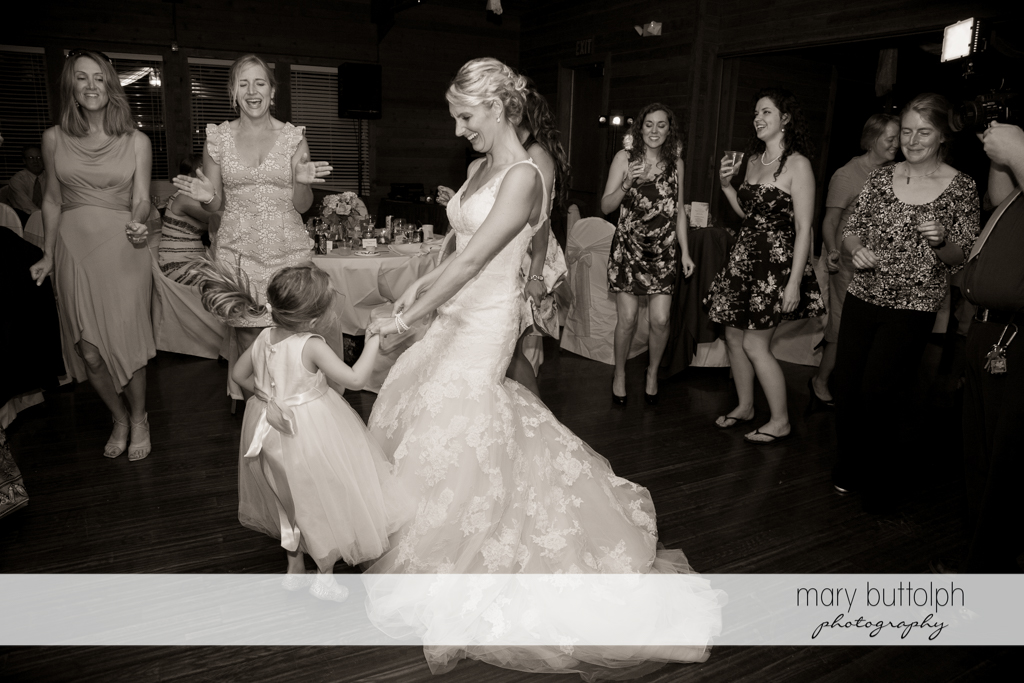 Bride dances with a young girl at the wedding venue at Arrowhead Lodge Wedding