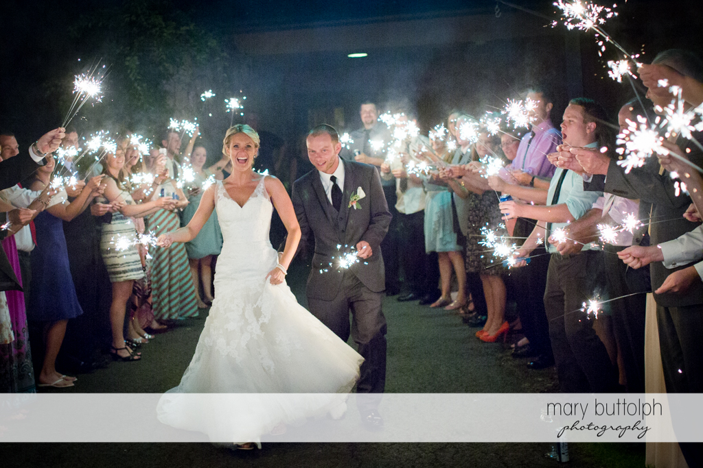 Couple and guests light up the night with sparklers at Arrowhead Lodge Wedding