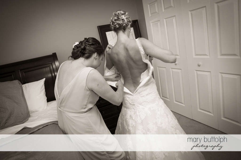 Bride's wedding gown is adjusted by a friend at Arrowhead Lodge Wedding