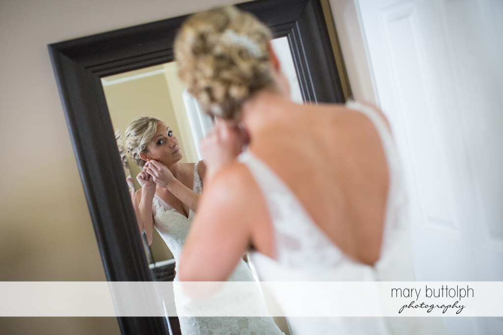 Bride puts on her earring in front of a mirror at Arrowhead Lodge Wedding