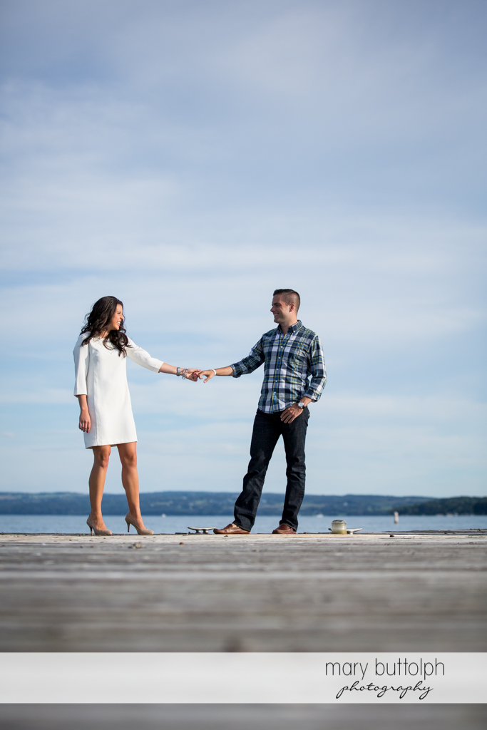 Couple stand in front of the lake at Skaneateles Country Club Engagement