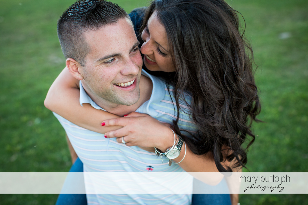 Man gives woman a piggyback ride in the garden at Skaneateles Country Club Engagement