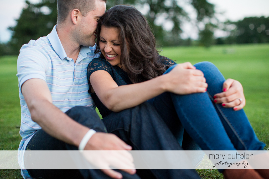 Couple sit on the grass in the park at Skaneateles Country Club Engagement