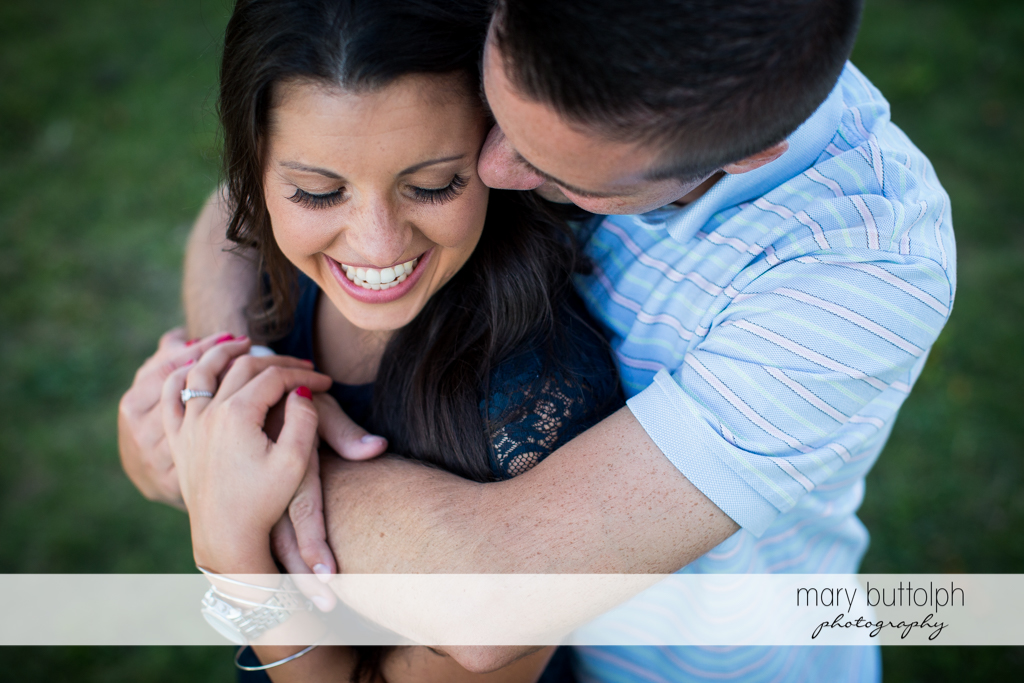 Couple share a happy moment in the garden at Skaneateles Country Club Engagement