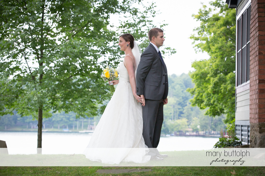 Couple stand back to back in the garden at the Hamilton Inn Wedding