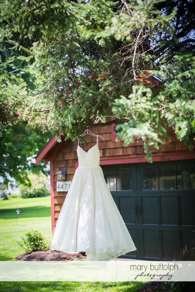 Bride's wedding gown hangs from a tree at the Hamilton Inn Wedding
