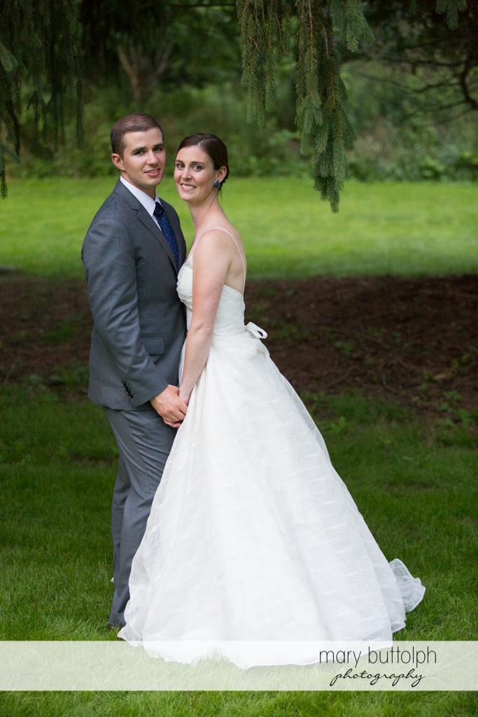 Couple hold hands in the woods at the Hamilton Inn Wedding
