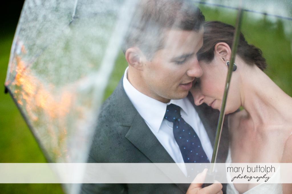 Couple get romantic as the rain falls in the garden at the Hamilton Inn Wedding