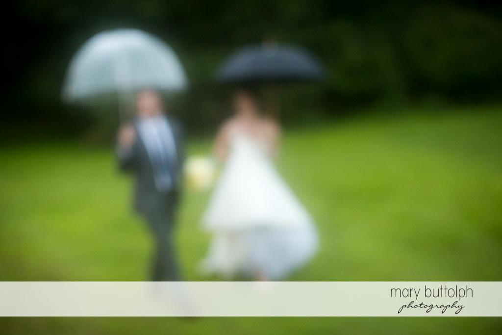 Trick shot of the couple with umbrellas in the garden at the Hamilton Inn Wedding