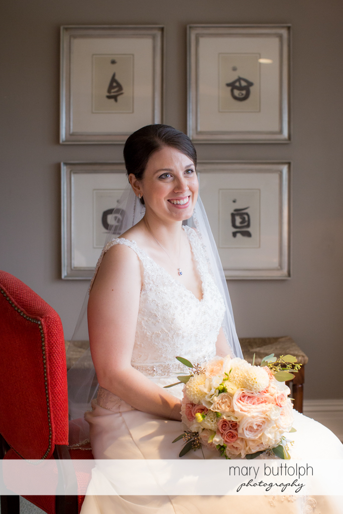 Bride with bouquet sits on a red chair at the Inns of Aurora Wedding