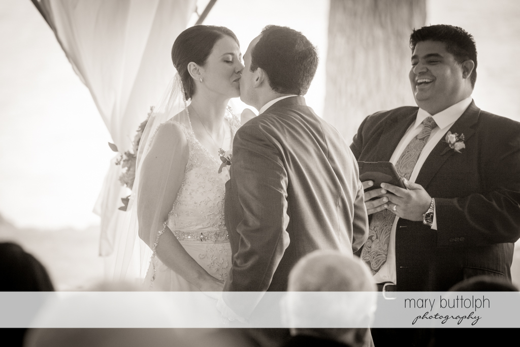 Couple kiss in front of the wedding officiant at the Inns of Aurora Wedding