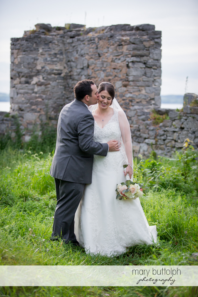 Groom kisses the bride in front of the ruins at the Inns of Aurora Wedding