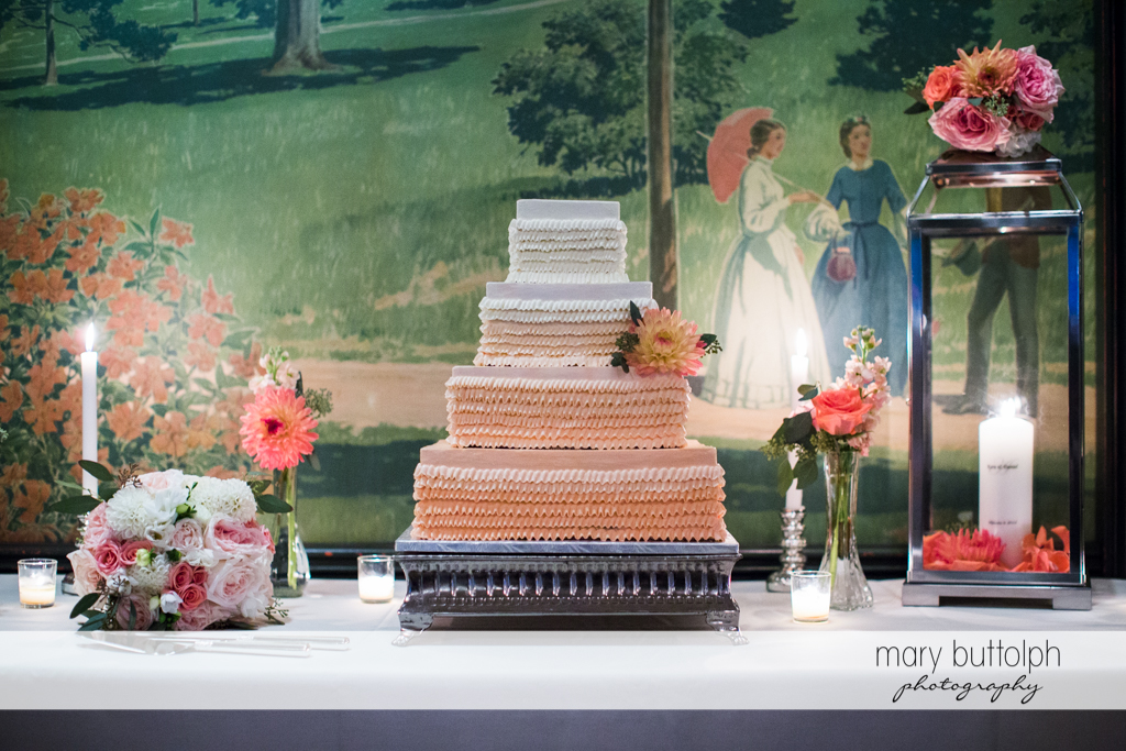 Couple's wedding cake sits on a table in front of a huge painting at the Inns of Aurora Wedding