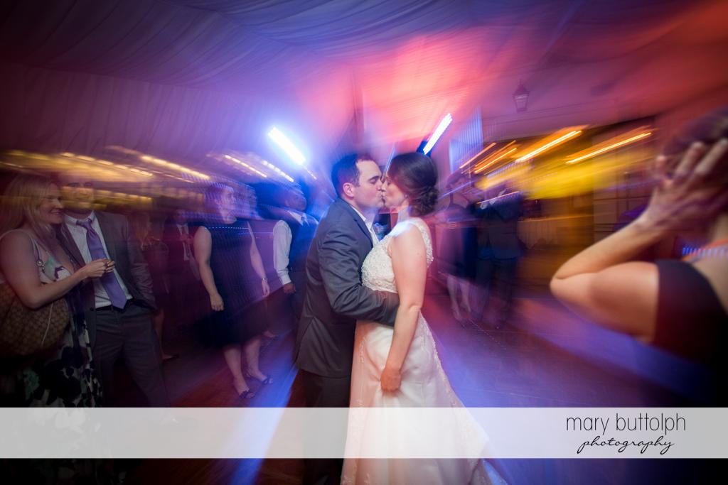 Couple kiss on the dance floor at the Inns of Aurora Wedding