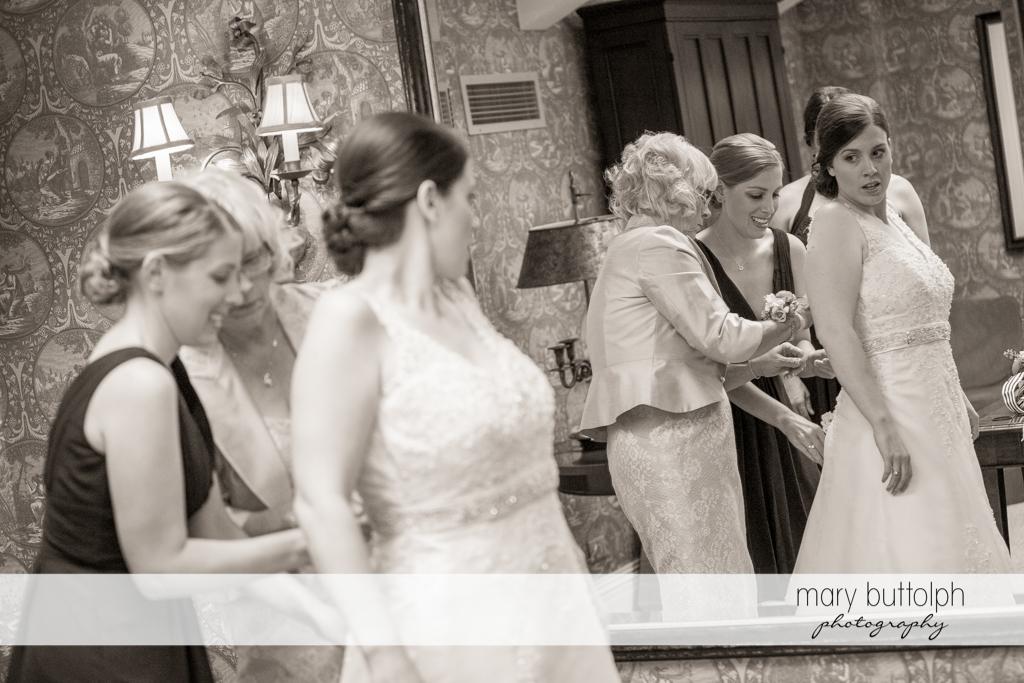 Friends help the bride put on her wedding gown at the Inns of Aurora Wedding