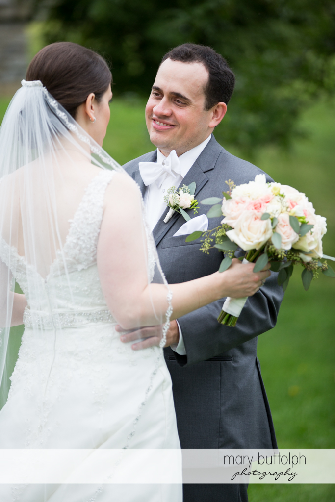 Groom faces the bride in the garden at the Inns of Aurora Wedding