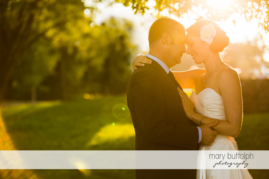 Couple share a romantic moment in the garden at Anyela's Vineyards Wedding