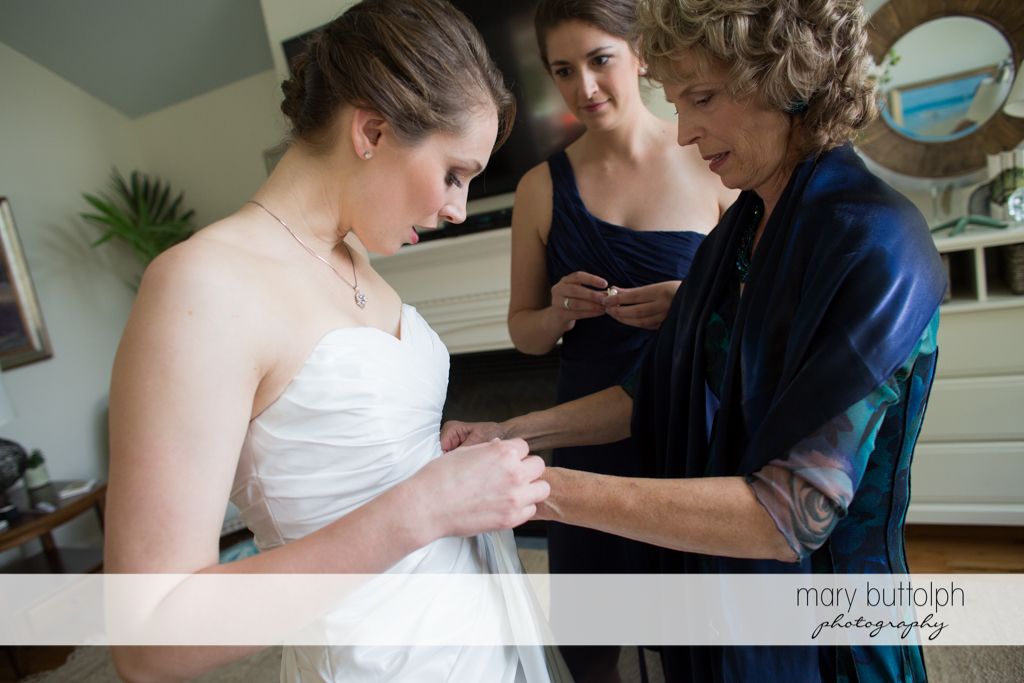 Bride gets a little help from her mother in putting on her wedding gown at Anyela's Vineyards Wedding