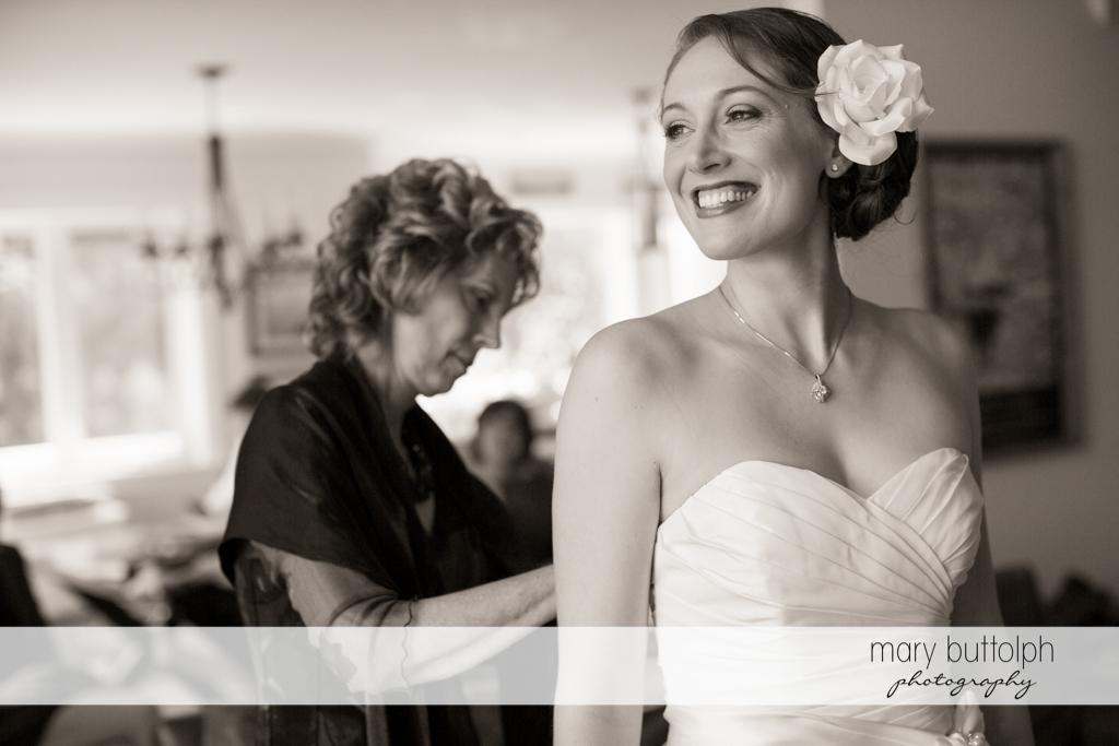 Bride smiles as her mother adjusts her wedding gown at Anyela's Vineyards Wedding