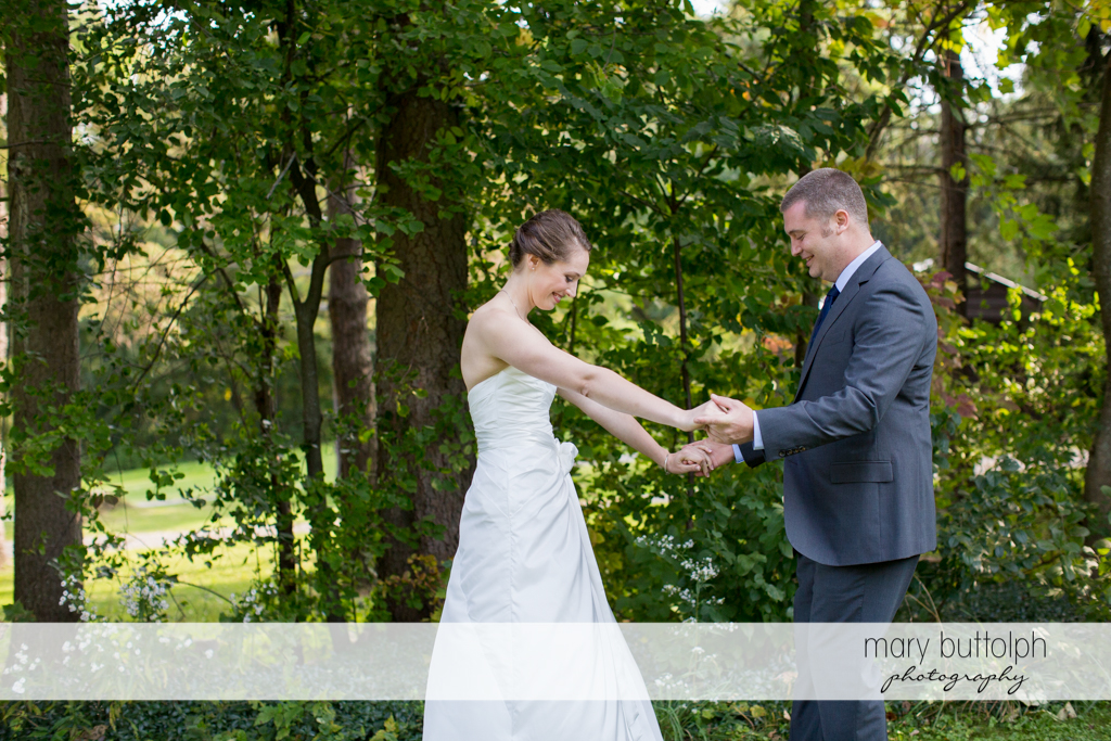 Couple hold hands in the garden at Anyela's Vineyards Wedding