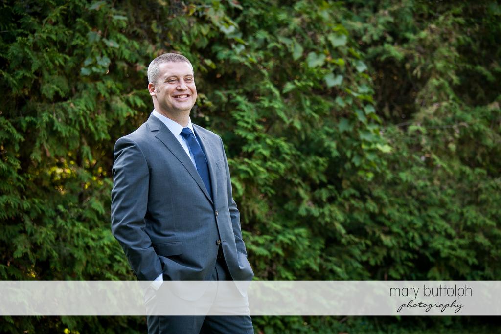 Groom stands in the garden at Anyela's Vineyards Wedding