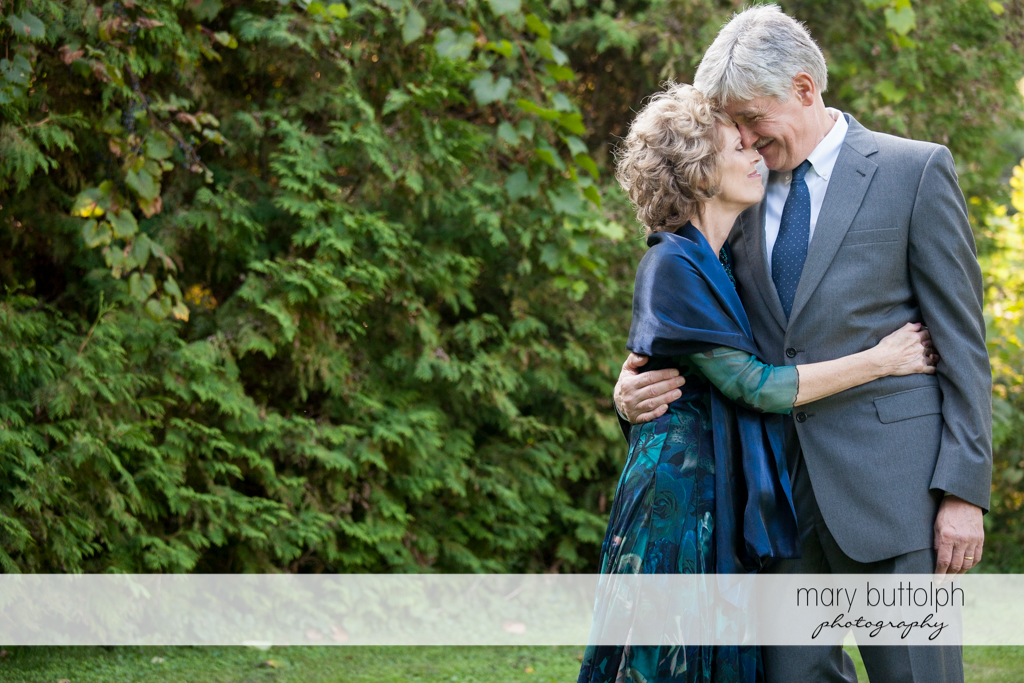 Bride's parents embrace in the garden at Anyela's Vineyards Wedding