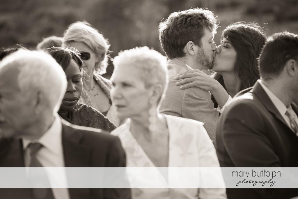 A couple kiss during the wedding ceremony at Anyela's Vineyards Wedding