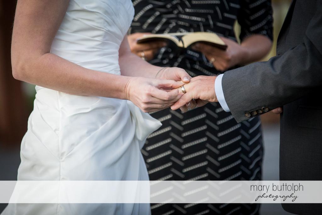 Bride slips on the groom's wedding ring during the garden wedding at Anyela's Vineyards Wedding