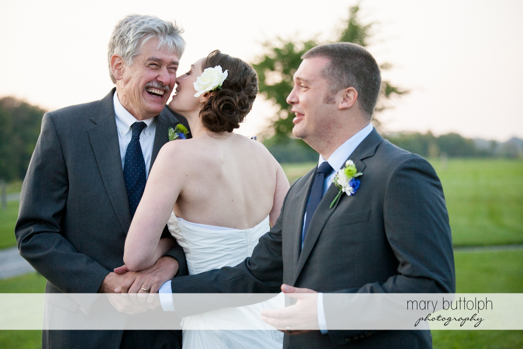 Bride kisses her father as the groom shakes his hand at Anyela's Vineyards Wedding