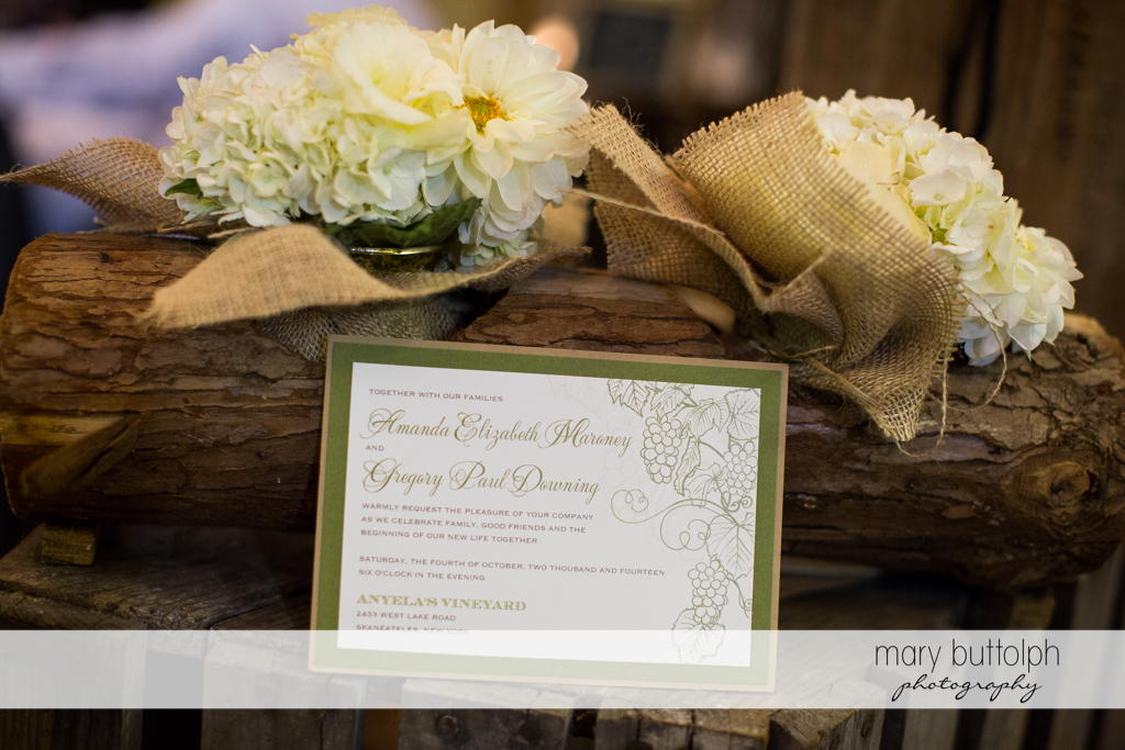 Couple's wedding program is propped up against a log with flowers at Anyela's Vineyards Wedding