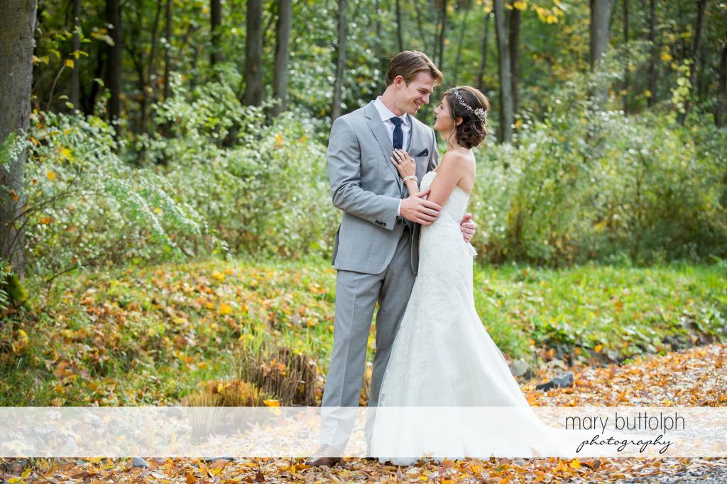 Couple embrace in the woods at Anyela's Vineyards Wedding