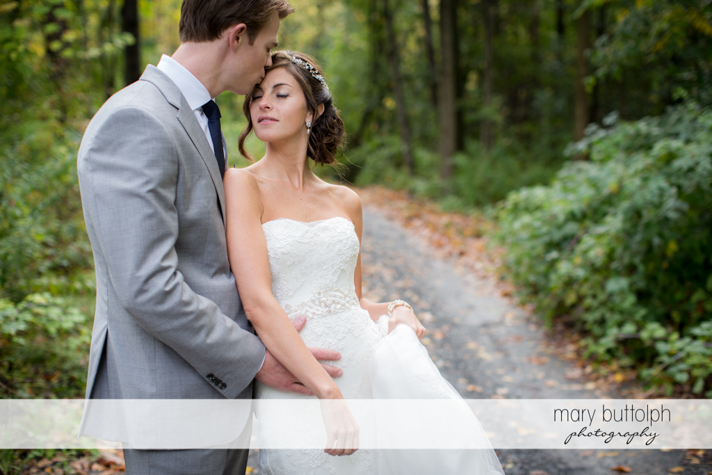 Couple share a romantic moment in the woods at Anyela's Vineyards Wedding