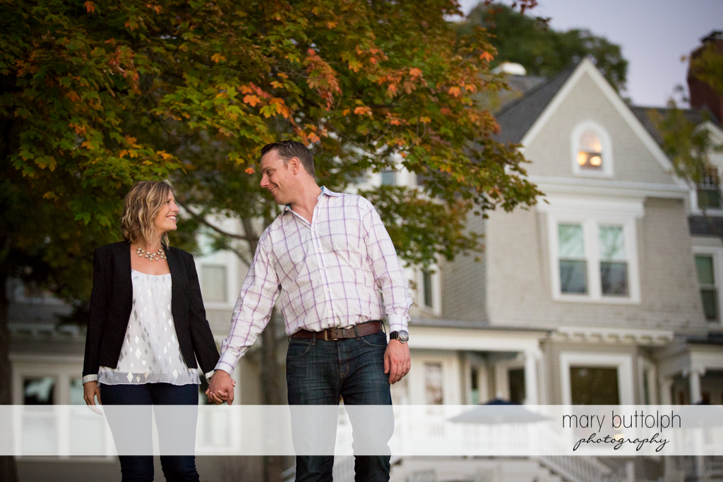 Couple stroll in front of a house at the Inns of Aurora Engagement